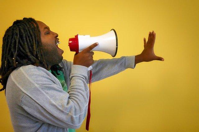 muž křičící do megafonu